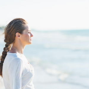 Woman practicing mindfulness looking at the ocean.