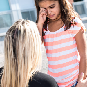 A teacher comforts a crying child.