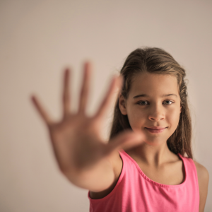 Girl holds up her hand to ask someone to stop during conflict.