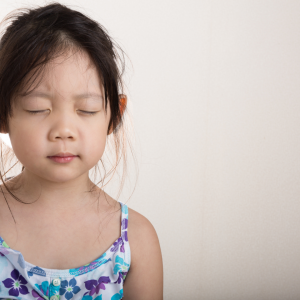 A young girl closes her eyes and breaths deeply.