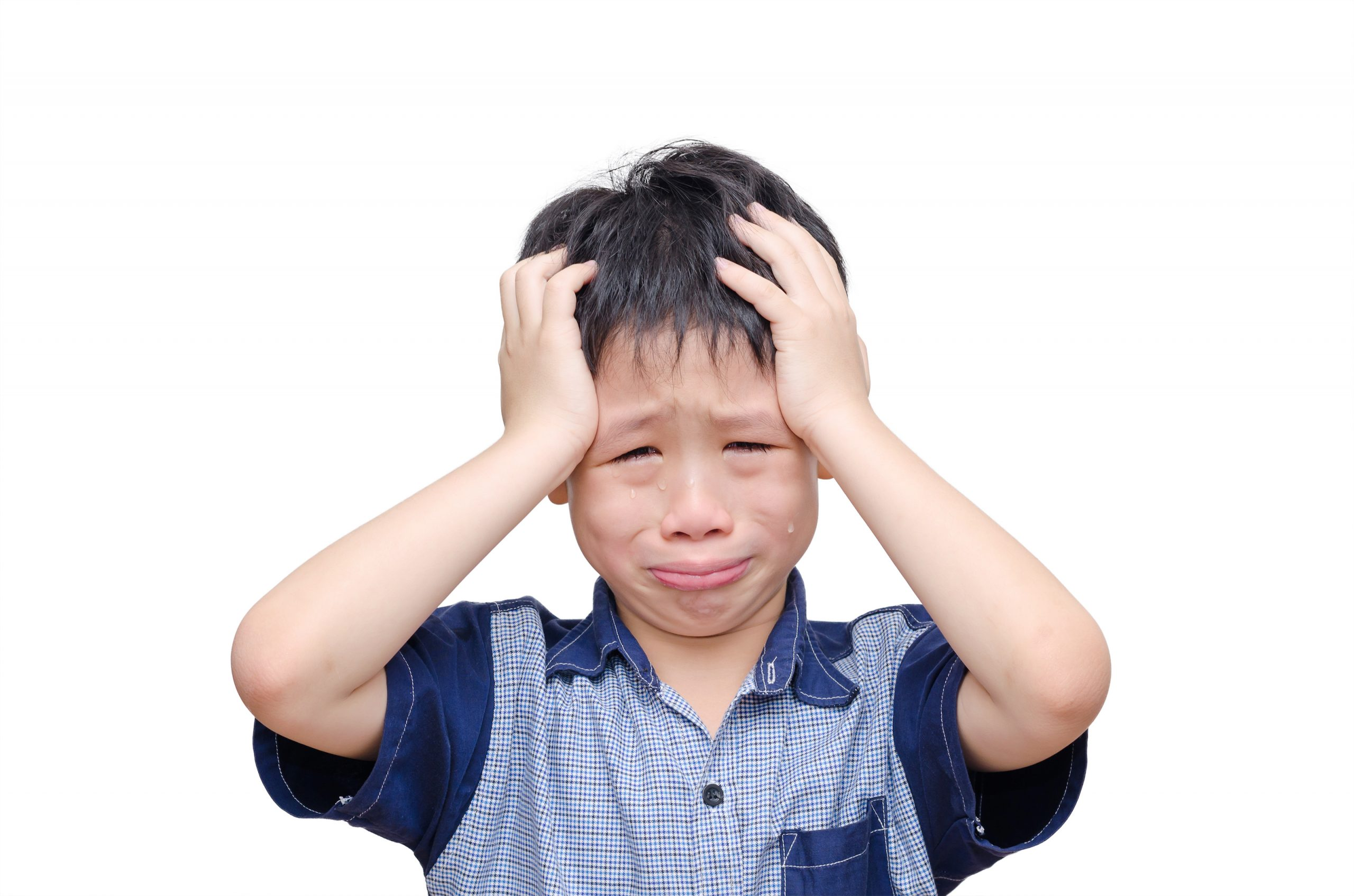 A crying boy puts his hands on his head.