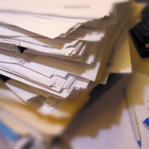 A pile of files and papers stacked high.