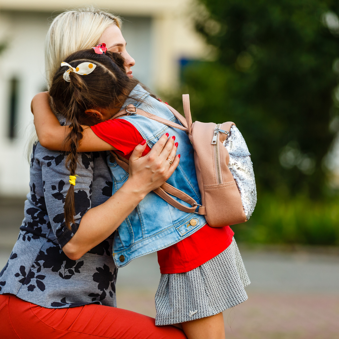 A teacher hugs and comforts a crying young student.