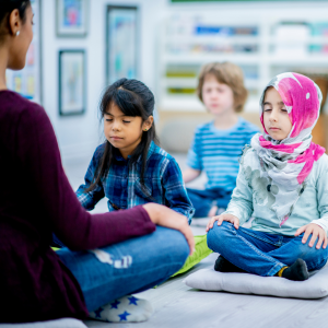 A teacher guides her students in deep breathing to help relieve the effects of her emotional labor.