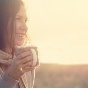 A happy, smiling woman holds a mug and looks out at nature.