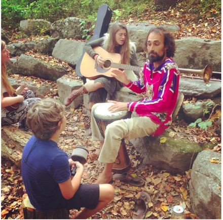 A woman and man play music with a guitar and drum for children.