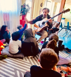 The author of this article plays his guitar for children.