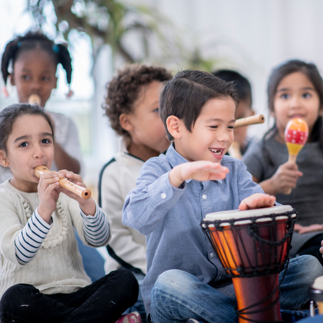 Young children playing the bongos and flute.